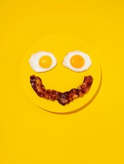 Anthropomorphic smiley face made of eggs and bacon yellow background