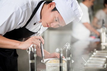 Young Asian chef plating food in a restaurant carefully pipetting garnish onto the side of a plate