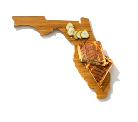 Toasted sandwich wrap and pickles on wooden cutting board