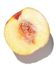 Halved peach sprinkled with sugar on white background