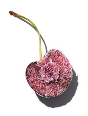 Cherry half sprinkled with sugar on white background