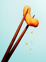 Close up junk food snack chopsticks against blue background