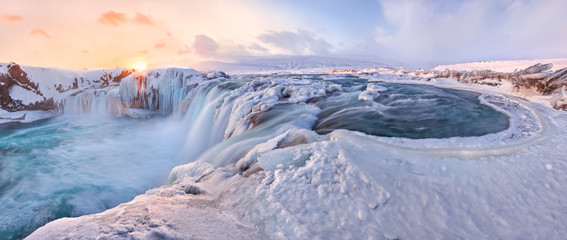 Godafoss frozen waterfall during Winter at sunrise. North Iceland