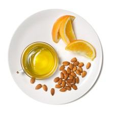 Plate of almonds, orange slices and glass of honey on white background