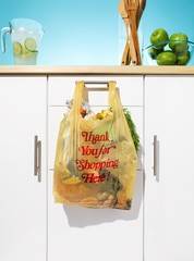 Plastic shopping bag with vegetables hanging counter drawer