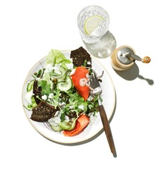 Plate of salad and pepper mill on white background