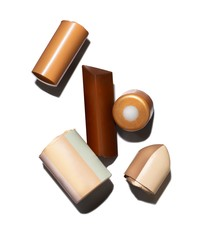 Pieces of brown and beige cosmetics on white background