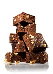 Stack of chocolate brownies with walnuts on white background