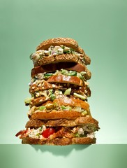 Low angle stack of bacon and chicken sandwiches on green background