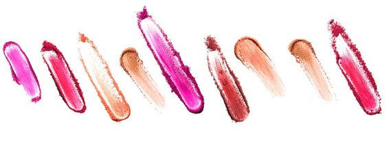 Row of smeared pink and beige powdered cosmetics on white background