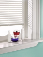 Cosmetics containers on windowsill with vertical blinds studio shot