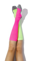 Legs of woman wearing one hot pink knee sock and one yellow knee sock on white background