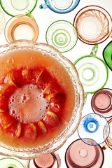 Bowl of fruit punch with grapefruit slices and empty glasses on white background