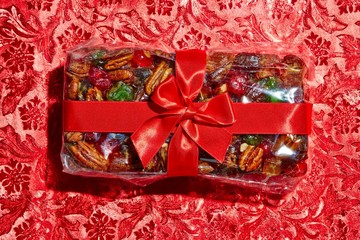 Top view fruitcake wrapped with red bow on red background