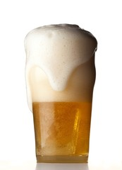 Froth overflowing glass of beer on white background