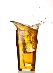 Full glass of beer splashing on white background
