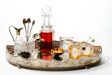 Glasses of alcohol and decanter tray with bowls of olives and orange peels