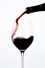 Red wine pouring into wineglass on white background