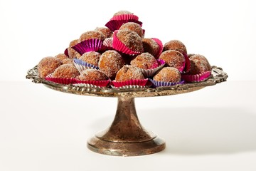 Wrapped pastry dough balls piled on metal cake tray on white background