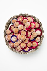 Top view wrapped pastry dough balls piled on metal cake tray on white background
