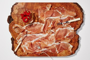 Overhead view of meat slices with red chili peppers cutting board