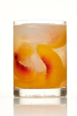 Cocktail glass with sliced peaches on white background