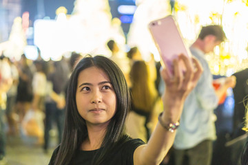 Young woman tourist laughing and taking selfie photo in bangkok., Female traveler and photographer takes selfie picture for her blog. technology concept. travel concept.
