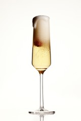 Foamy overflowing champagne flute on white background