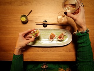 Top view woman eating sushi dinner with wineglass