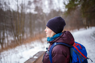 Photo of side view of woman with backpack on blurred background in forest
