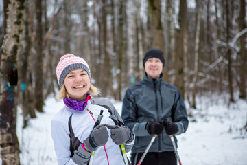 Image of cheerful sports woman and man skiing in winter forest