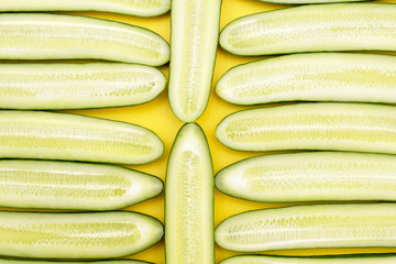cucumbers are laid out in a row on a yellow background