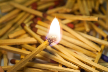match sticks spread on white paper and match burning in center abstract