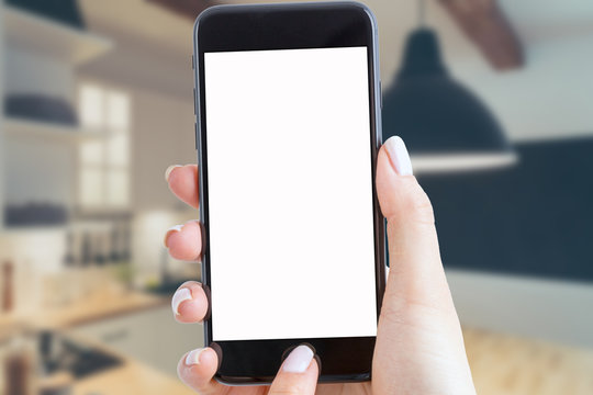 smartphone holds a hand in the kitchen