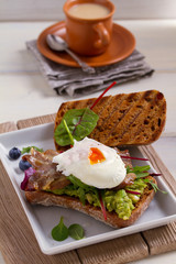 Poached egg, bacon, smashed white bean and avocado on toast. Sandwich. vertical