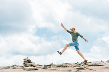 Sport activity at top of mountain. Professional sporstman jumping forward outdoor at nature. Conquering new mountains. Overcoming progress. Summer fun. Unusual traveler stepping stones. Successful boy