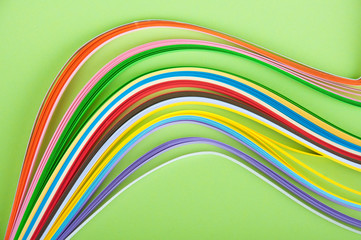 Colored waves of long paper strips laying on green background