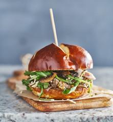 vegan sandwich with meatless crumbles on pretzel bun