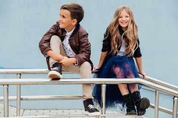 Children, a boy and a girl are sitting on the railing in the park friends. Concept of friendship.
