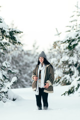 A beautiful girl walks through the snowy winter coniferous forest.