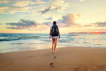 Woman with backpack walk on the ocean sand beach at sunset time