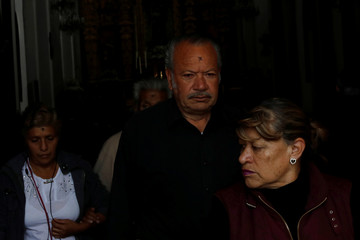 Devotees with an ash cross on their forehead come out of a local church on Ash Wednesday, in Mexico City