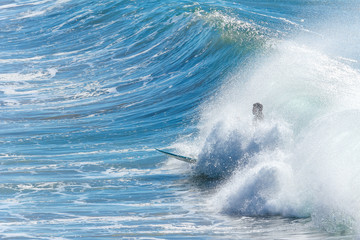 Surfer in large wave wipes out and falls off surf board