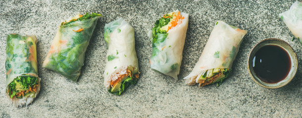 Helathy Asian cuisine. Flat-lay of vegan spring rice paper rolls with vegetables, soy sauce, chopsticks over concrete background, top view, wide composition. Clean eating, dieting, vegetarian food