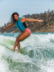 Mixed race fit young woman wakesurfing on a lake in California on a clear summer day