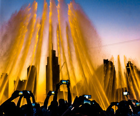 Low Angle View Of People Photographing Fountain From Mobile Phones