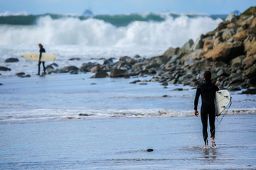 Surfer walks toward water at a popular surf location on a beautiful clear day