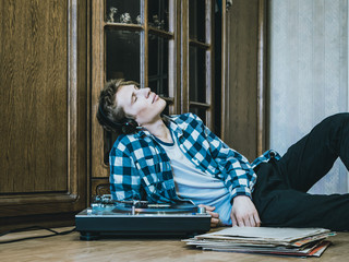 young male lying and listening to the music dreaming and relaxing
