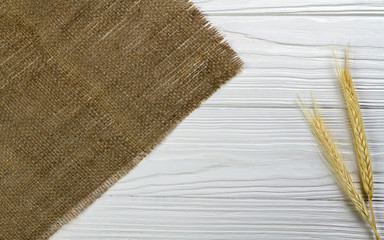 Wheat stalk and hessian fabric on white wooden background