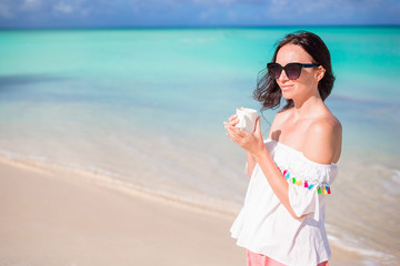 Young woman with hot coffee enjoying beach view.